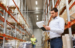 Businessman writing to clipboard at warehouse Royalty Free Stock Photography