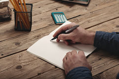 Businessman writing to notebook on a wooden table Royalty Free Stock Image