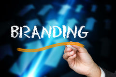 Businessman writing the word branding. Against blue arrows on black background Stock Image