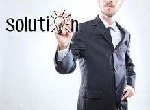 Businessman writing the word solution Stock Image