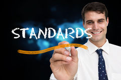 Businessman writing the word standards Stock Photo