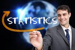 Businessman writing the word statistics Stock Image