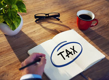 Businessman Writing the Word Tax on Note Pad. Businessman Writing the Word Tax Royalty Free Stock Photography