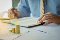 Businessman writting note paper with stacked coins arranged at o. Ffice desk and many document data graph in morning light, business concept Royalty Free Stock Photography