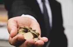 Businessman& x27; as mãos de s têm completamente de moedas douradas Fotografia de Stock Royalty Free