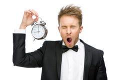 Businessman yawns keeping alarm clock Stock Photos