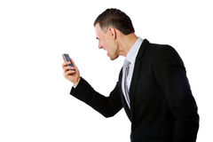 Businessman yelling on his cell phone. Angry businessman yelling on his cell phone over white background Royalty Free Stock Photos