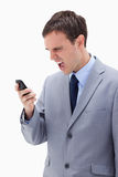 Businessman yelling at his cellphone. Against a white background Royalty Free Stock Image
