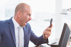 Businessman yelling at his phone Stock Images
