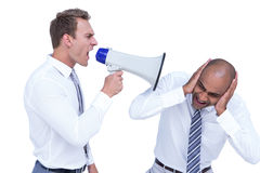 Businessman yelling with a megaphone at his colleague Stock Image