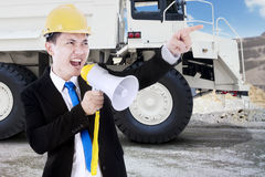Businessman yelling in the mining site. Young businessman, yelling uses a megaphone in the mining site with a big truck on the background Stock Photos
