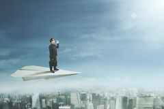 Businessman yelling on paper plane. Businessman flying above a city with a big paper plane and yelling at the sky Royalty Free Stock Images