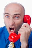 Businessman yelling into phone. A view of an angry and upset businessman yelling into the handset of a bright red telephone Royalty Free Stock Photos