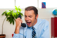 Businessman yelling during the phone call. Why are sales so low today? Businessman yelling on phone in his office Royalty Free Stock Photo