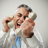 Businessman yelling into phone Stock Photos
