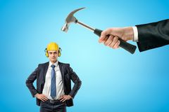 Businessman in yellow hard hat with ear defenders, standing with hands on hips, and big hand holding hammer to his head. royalty free stock photography