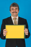 Businessman with yellow sign. Happy middle aged businessman with blank yellow sign or clip chart, blue studio background Royalty Free Stock Photo