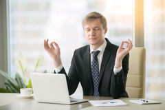 Businessman in yoga pose in the office. Young calm businessman working with laptop in yoga pose at modern office desk, minimize day discomfort, focusing on work stock image