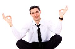 Businessman in yoga pose showing OK sign Royalty Free Stock Images