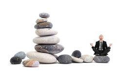 Businessman in yoga position on a pebble compositi Royalty Free Stock Images