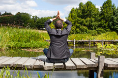 Businessman yoga praying on wooden path above water Stock Photos