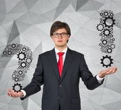 Businessman. Young businessman holding question and exclamation mark Stock Photos
