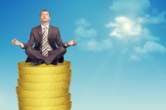 Businessmanin in lotus posture on coins stack Royalty Free Stock Photography
