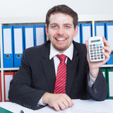 Businessmann in a black suit at office with calculator Stock Image