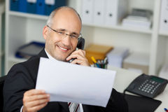 Businessmann reading document while calling Stock Photo
