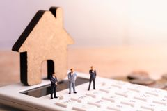 Businessmans和房子模型在计算器有词税的 库存图片