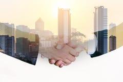 businessmans握手两次曝光特写镜头在城市背景的 库存图片