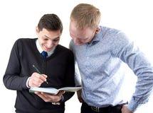 2 businessmans на белый смотреть в книге Стоковые Фотографии RF