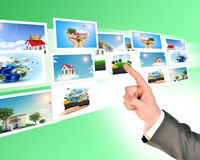 Businessmans arm touching holographic pictures Royalty Free Stock Photo
