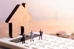 Businessmans e modelo da casa na calculadora com o imposto da palavra imagens de stock