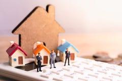 Businessmans et modèle de maison sur la calculatrice avec l'impôt de mot photographie stock