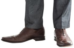 Businessmans feet in brown brogues Stock Photos