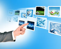Businessmans finger pointing at pictures Stock Photo