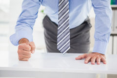 Businessmans fist clenched over desk Royalty Free Stock Images