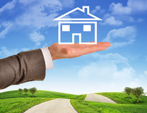 Businessmans hand holding wire-frame house Stock Photos