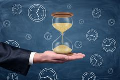 A businessmans hand turned palm up and holds a large functioning hourglass on blue chalkboard background. Master of time. Bending your schedule. Find time for Royalty Free Stock Photo