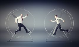 Challenge at work. Businessmans run in hamster wheele for competition royalty free stock image