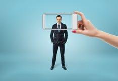 Businessmans stellen im Fokus gegenüber, der durch den Rahmen des Telefons sieht Lizenzfreie Stockbilder