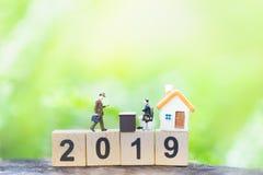 Businessmans und Haus auf Holzklotznummerjahr 2019 auf Gr?nnaturhintergrund stockbilder