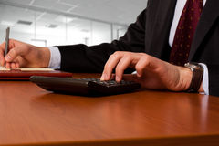 Businessmanworking working with a calculator Stock Photography