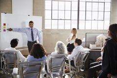 Businessmastands genom att använda whiteboard under en presentation royaltyfri foto