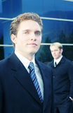 Businessmen. Two business men standing one in front of the other with blue office building in background Royalty Free Stock Image
