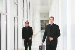 Businessmen. Two businessmen walking in hallway Stock Photos