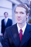 Businessmen. Two businessmen standing looking at camera in full suit in front of building Royalty Free Stock Images