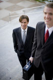 Businessmen. Two businessmen standing on steps in suits holding briefcase looking up Royalty Free Stock Images