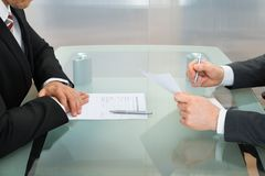 Businessmen with application form on office desk Royalty Free Stock Images